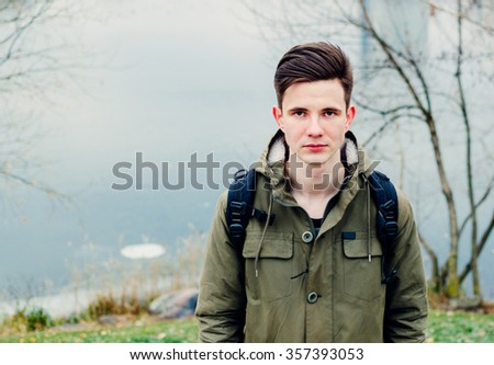 Portrait of the young man on the autumn city river - stock photo