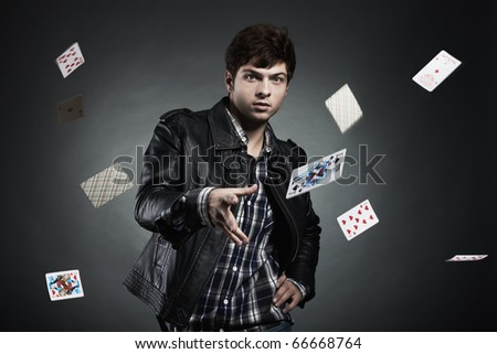 Portrait of the young man playing cards - stock photo