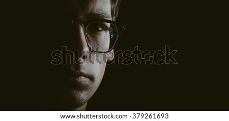 Portrait of the young man with glasses in low key  - stock photo