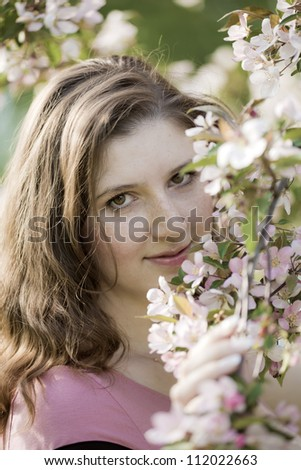 Portrait of the young woman against a blossoming apple-tree - stock photo