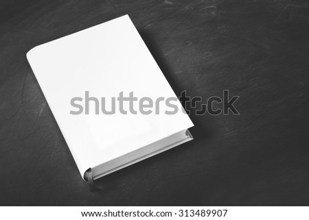 portrait of thick book with white cover on black board for background with copy space - stock photo
