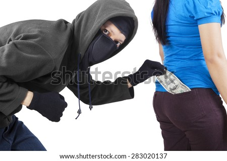 Portrait of thief wearing mask and jacket, taking money from pocket of woman - stock photo