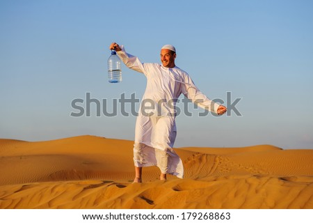 Portrait of thirsty Arabic man on a middle of yellow desert. - stock photo
