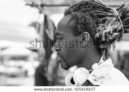 Portrait of thoughtful black man outdoor in a weekly clothes market - Young rasta guy with headphones in New York - Love sadness concept - Black and white editing - Soft focus on face - Warm filter - stock photo