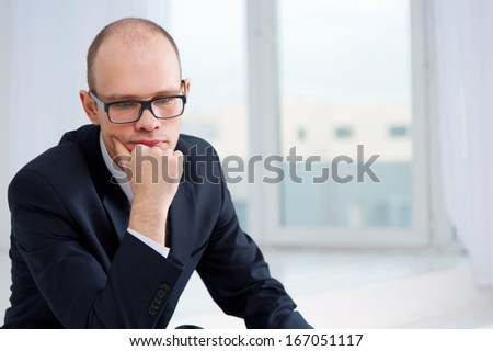 Portrait of thoughtful business man in office with view to window - stock photo
