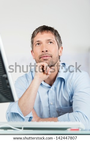 Portrait of thoughtful businessman with computer at desk in office - stock photo