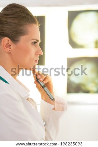 Portrait of thoughtful medical doctor woman in front of tomography lightbox - stock photo