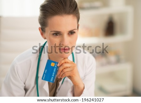 Portrait of thoughtful medical doctor woman with credit card - stock photo