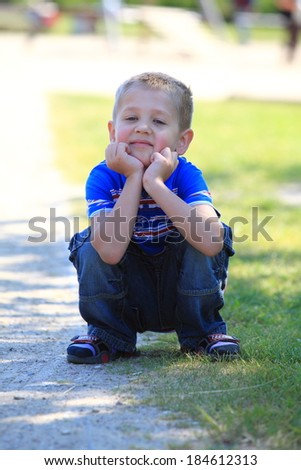 Portrait of thoughtful, pensive little boy child or kid in summer park - stock photo