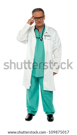 Portrait of thoughtful senior doctor posing with finger on his head - stock photo