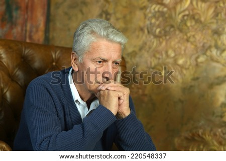 Portrait of thoughtful senior man at home - stock photo