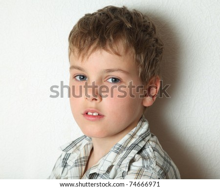 Portrait of thoughtful young blonde boy in chequered shirt, about 8 years old - stock photo
