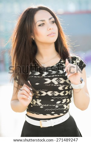 Portrait of thoughtful young brunette posing outdoors - stock photo