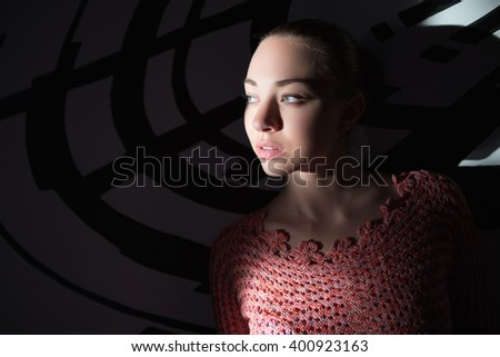Portrait of thoughtful young lady wearing knitted sweater posing near wall - stock photo