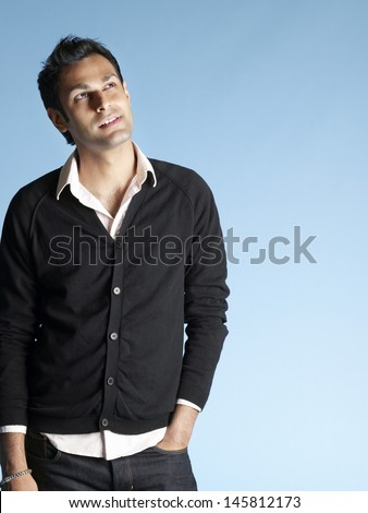 Portrait of thoughtful young man looking up at copyspace isolated on blue background - stock photo