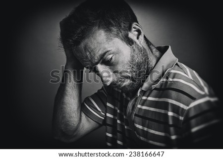 Portrait of thoughtful young man scratching his head, looking down. Black and white style picture. - stock photo