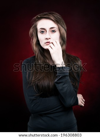 Portrait of thoughtful young woman on red dark background - stock photo