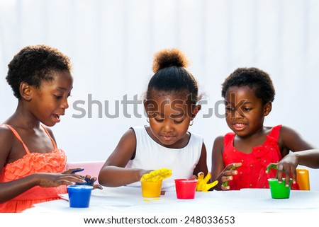 Portrait of three African kids painting with hands.Isolated against light background. - stock photo