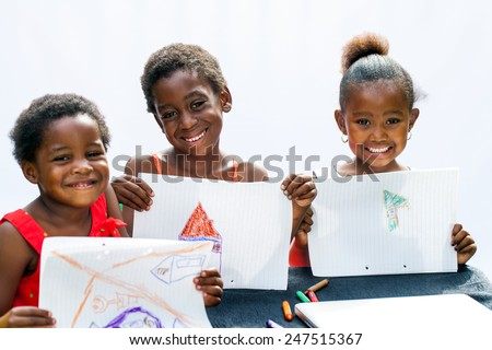 Portrait of three African youngsters showing their drawings at desk.Isolated on light background. - stock photo