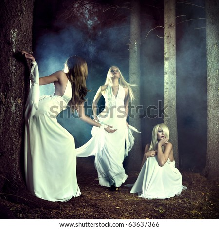 Portrait of three beautiful nymphs in misty forest - stock photo
