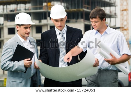 Portrait of three builders standing at building site and discussing new project held by one of men - stock photo