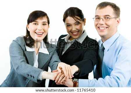 Portrait of three business partners making pile of their hands and looking at camera with smiles - stock photo