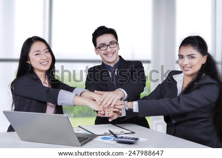 Portrait of three business people smiling at the camera while joining hands - stock photo