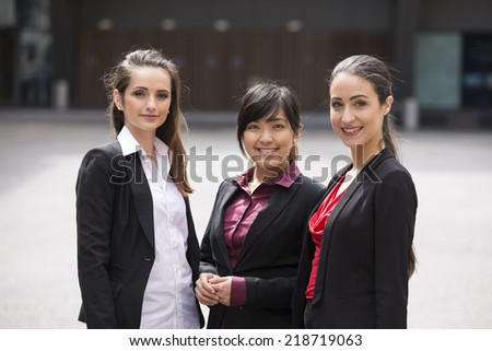 Portrait of three business women standing in a row. Interracial group of business women. - stock photo