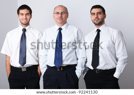 Portrait of three businessman, all keep hands in their pockets - stock photo