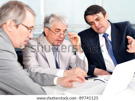 Portrait of three businessmen at the computer. Office background. - stock photo