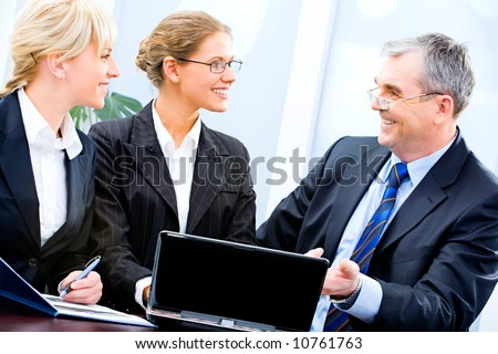 Portrait of three businesspeople sitting near laptop and discussing working ideas in the office - stock photo