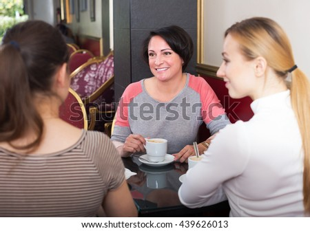 Portrait of three cheerful woman sitting in the cafe and talking with each other - stock photo