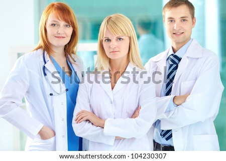 Portrait of three clinicians in white coats looking at camera - stock photo