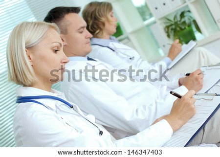 Portrait of three clinicians with clipboards making notes at medical conference - stock photo