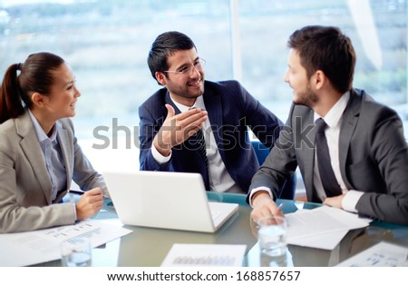 Portrait of three co-workers discussing business plan in office - stock photo