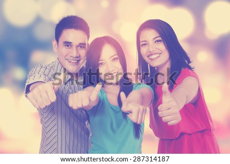 Portrait of three college students showing thumbs up on the camera, shot with bokeh background - stock photo