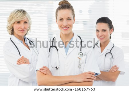 Portrait of three confident female doctors standing with arms crossed at the medical office - stock photo