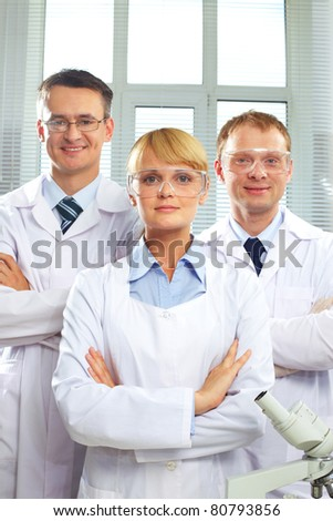 Portrait of three doctors looking at camera and smiling - stock photo