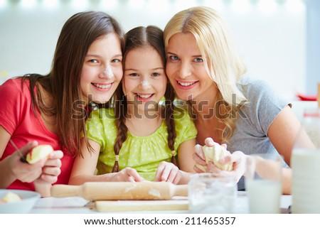 Portrait of three females at the kitchen - stock photo