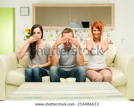 portrait of three friends sitting on couch imitating see no evil, hear no evil, speak no evil conept - stock photo