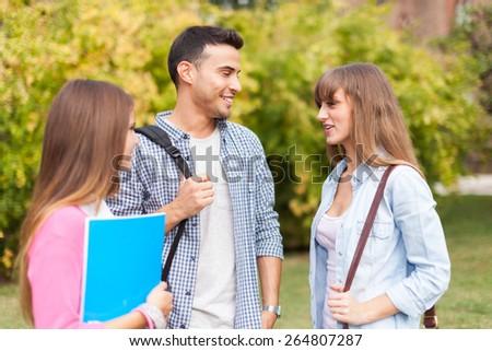 Portrait of three friends talking in a park - stock photo