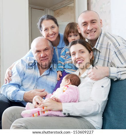 Portrait of three generations family sits on sofa in livingroom at home - stock photo