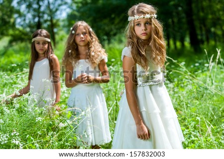 Portrait of three girl friends wearing white dresses in woods. - stock photo