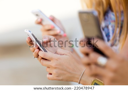 Portrait of three girls chatting with their smartphones at the park  - stock photo