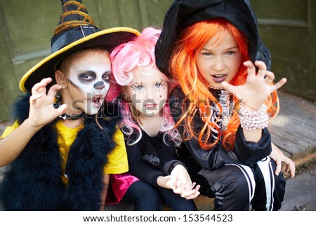 Portrait of three Halloween girls looking at camera with frightening gesture - stock photo