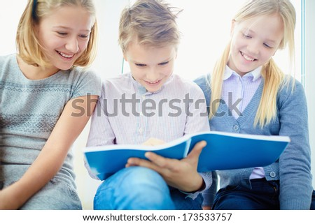 Portrait of three happy classmates looking at notes in exercise book of schoolboy while he writing - stock photo