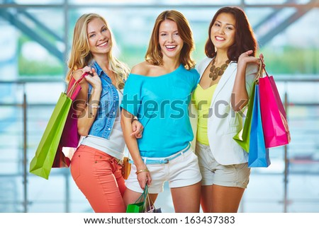 Portrait of three happy girlfriends in smart casual looking at camera - stock photo