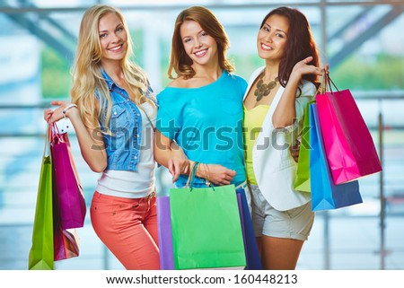 Portrait of three happy girls in smart casual holding paperbags - stock photo