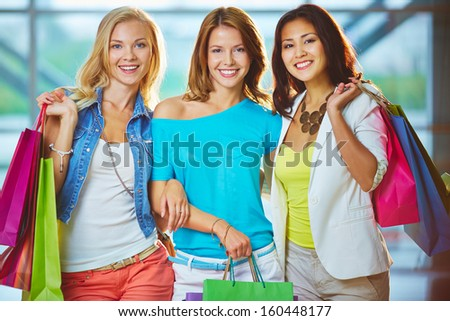 Portrait of three happy girls with paperbags looking at camera - stock photo