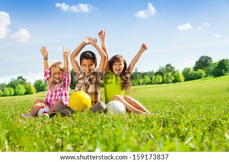 Portrait of three happy kids, boy and girls sitting in the grass in park with lifted hands and holding sport balls - stock photo